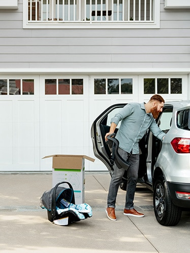 Man puts car seat into SUV in front of garage.
