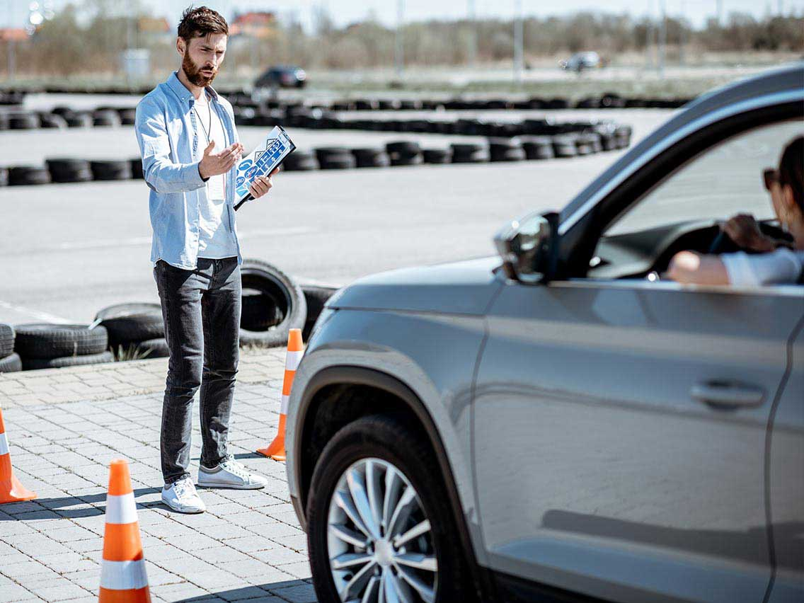 Teenager practicing parking with a driving instructor.