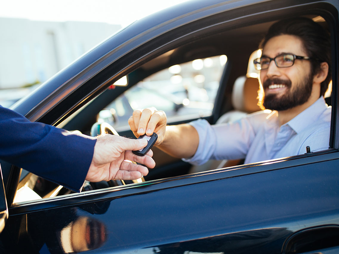 Man taking the keys to the car he just bought