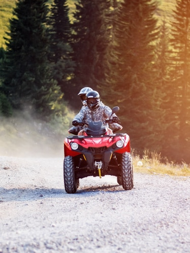 Two people riding on atv on dirt road