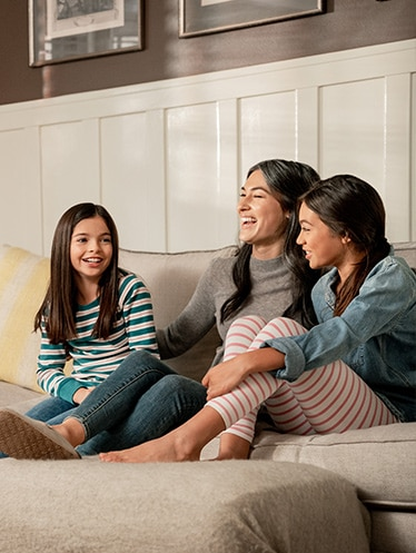 Mother sitting on couch with daughters