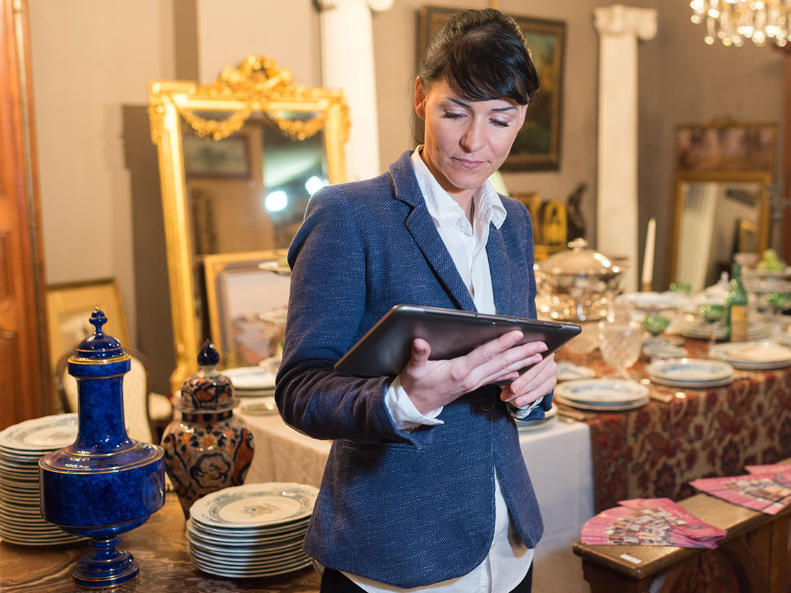 woman in antique shop holding an ipad