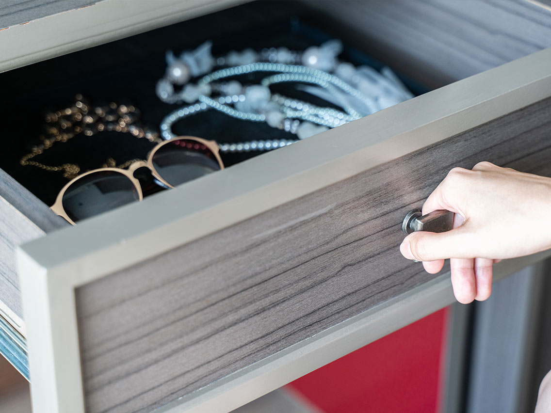 sunglasses, necklaces and jewelry being pulled out of a drawer