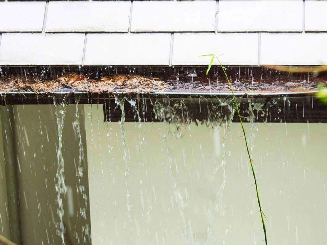 rain water overflowing blocked gutters