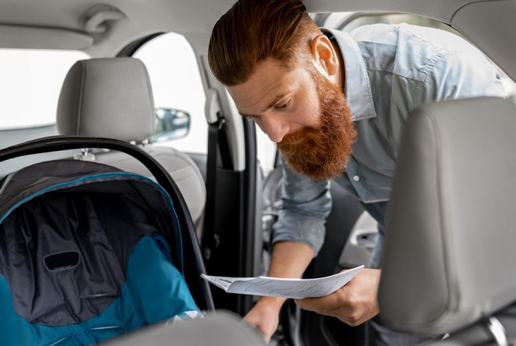 Man reads instructions to install child car seat in his vehicle.