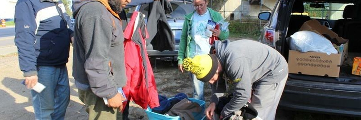 handing out winter clothing at a homeless camp
