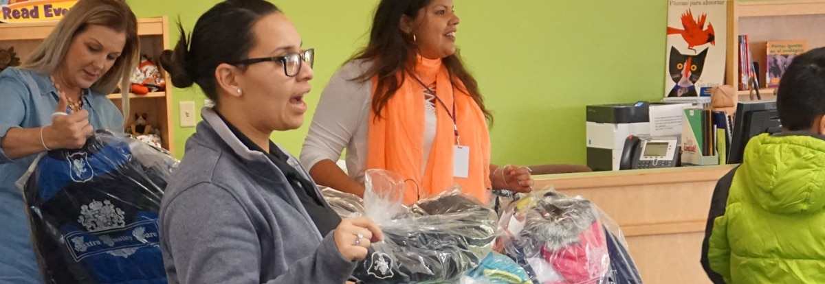 agents hand out donated coats to students