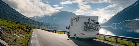 RV driving on a mountain road in the sun.