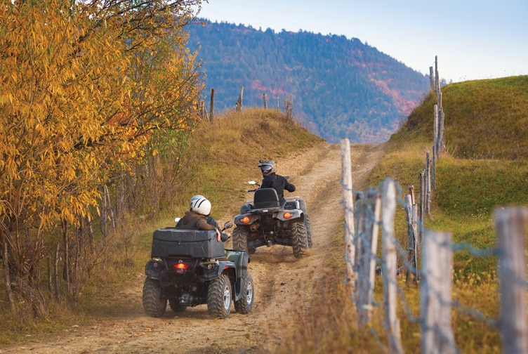 Two ATV riders ride a dirt path.