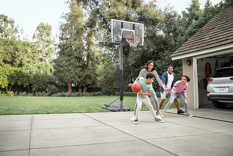 Family plays basketball in their driveway.