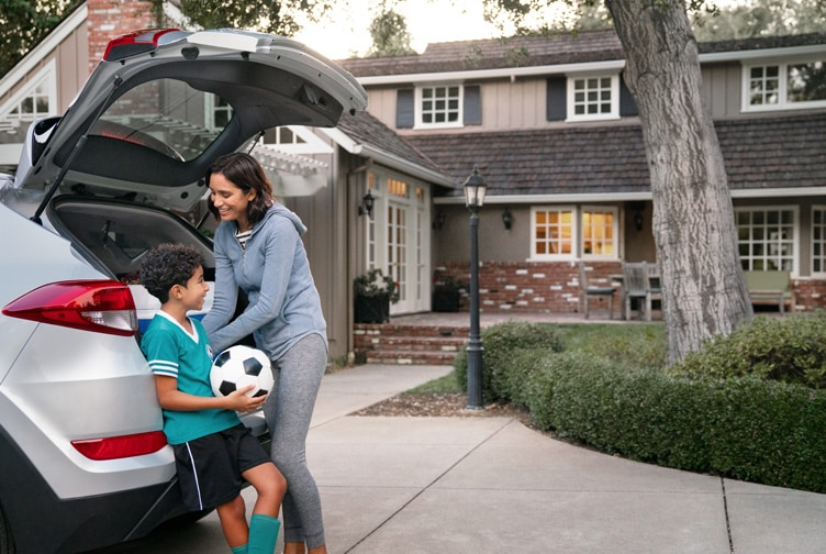 Son holding a soccer ball with his mother packing their vehicle.
