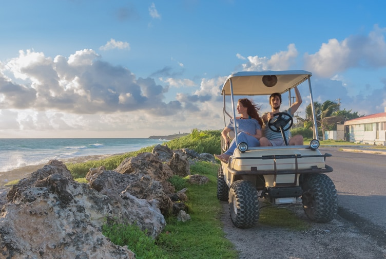 Couple in a golf cart driving on the course.