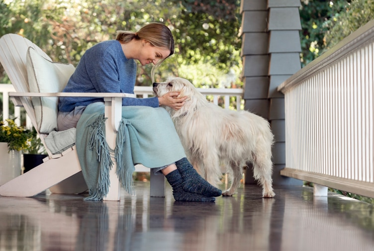 Woman pets her dog on her porch.