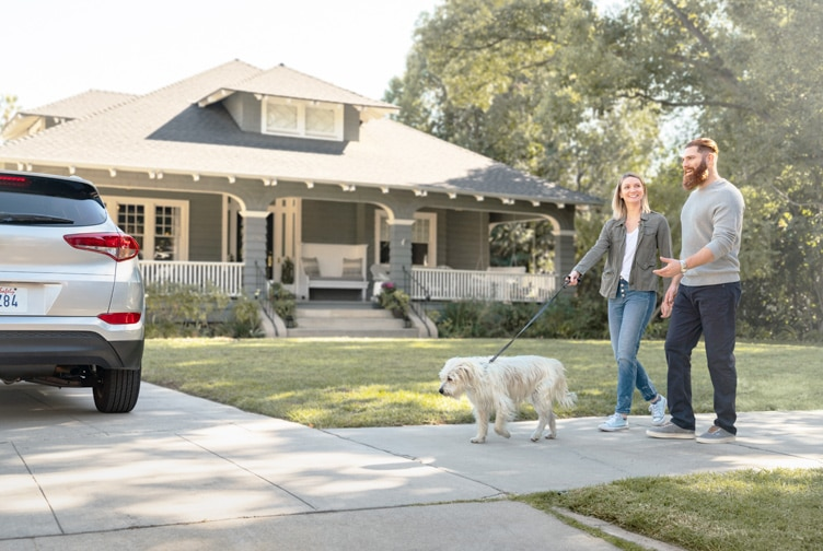 Family walks their dog in front of their home.
